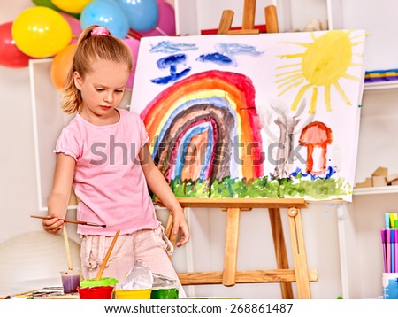 Child painting at easel in school. Education of small girl. - stock photo