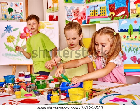 Child painting at easel in school. Teacher help. - stock photo