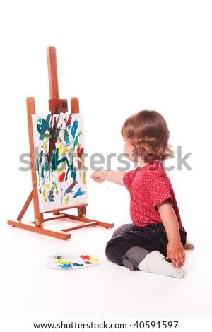 Child painting on easel with paintbrush - stock photo