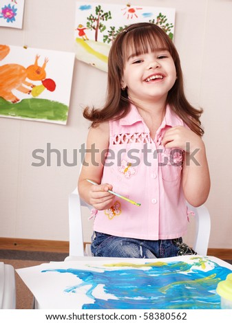 Child painting picture  in play room. Preschool. - stock photo