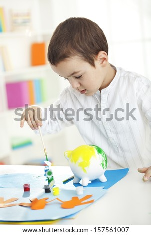Child painting piggy bank - stock photo