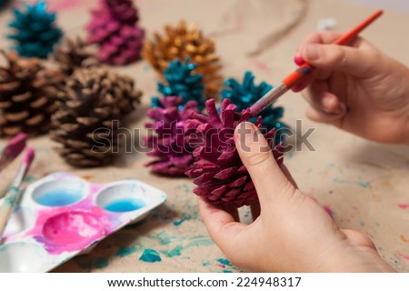 Child painting pine cones as homemade Christmas ornaments. - stock photo