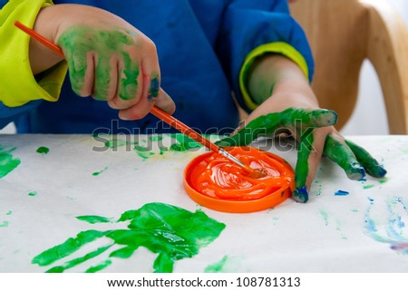 Child painting with finger paint and a brush - stock photo