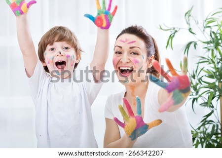 Child painting with mum - stock photo