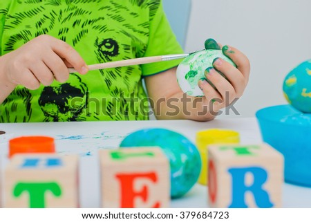 child paints the Easter eggs - stock photo