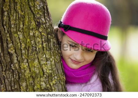 Child peeking behind a tree - stock photo