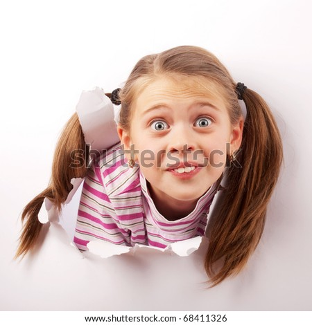 child peeps through a hole torn in the paper - stock photo