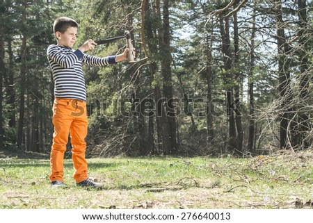 Child play with sling toy in the forest. - stock photo