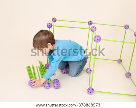 Child playing and building a fort or house using a construction set - stock photo