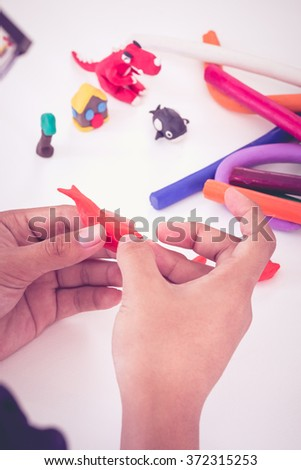 Child playing and creating toys from play dough. Child molding modeling clay. Strengthen the imagination of child. Vintage picture style. - stock photo