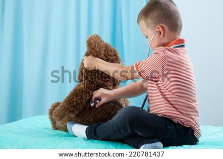 Child playing at doctor with his teddy bear - stock photo