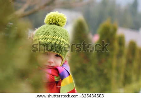 Child playing hide and seek behind the bushes - stock photo