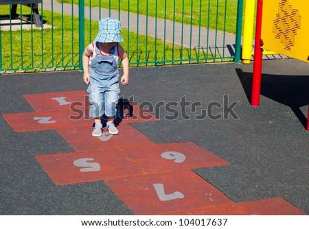 Child playing hopscotch - stock photo
