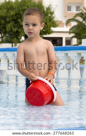 Child playing  in a hotel resort swimming pool in shallow water with a red toy bucket. - stock photo