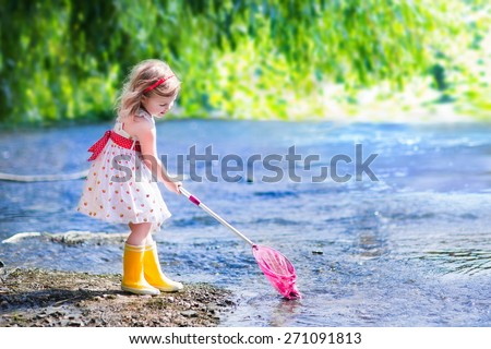 Child playing in a river. Cute little girl in summer dress and rain boots catching fish and frog with a colorful net standing in water. Kids play outdoors. Young explorer and fisherman in wild nature. - stock photo