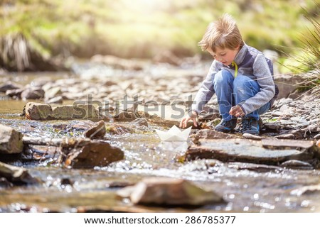 Child playing in summer sunshine with a paper boat in stream - stock photo
