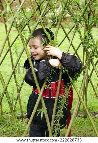 Child playing in willow handmade structure in a garden - stock photo