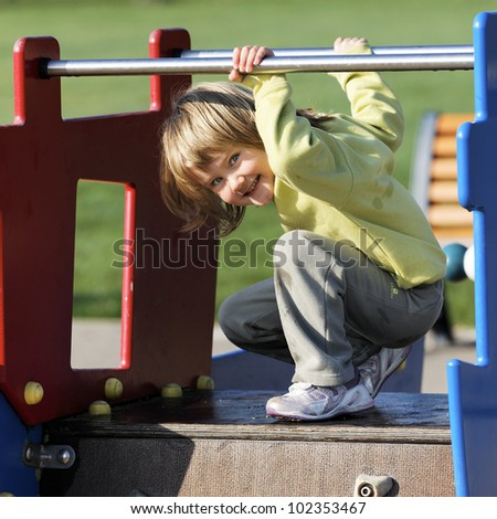 child playing on colorful playground in a park - stock photo