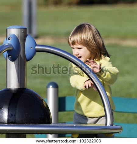child playing on playground in a park in autumn - stock photo