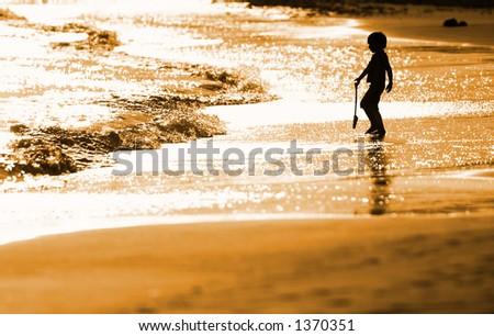 Child playing on the seashore - stock photo