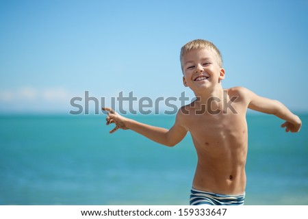 Child playing outdoors at the sea - stock photo