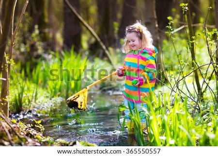 Child playing outdoors. Preschooler kid catching frog with colorful net. Little girl fishing in river in summer. Adventure kindergarten day trip into wild nature, explorer hiking and watching animals. - stock photo