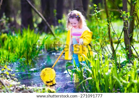 Child playing outdoors. Preschooler kid catching frog with colorful net. Little girl fishing in a forest river. Adventure kindergarten day trip into wild nature, explorer hiking and watching animals. - stock photo