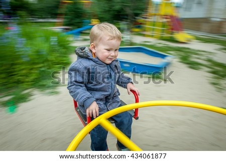 Child, Playing, Playground, summer, childhood, leisure and people concept - happy little boy on children playground  - stock photo