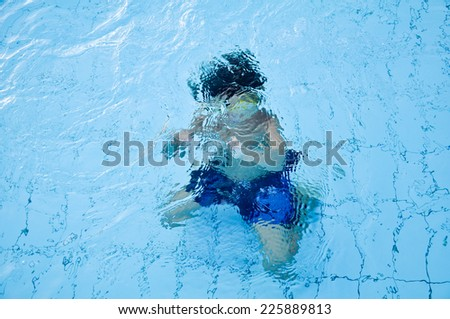 Child playing underwater in a swimming pool shot from outside - stock photo