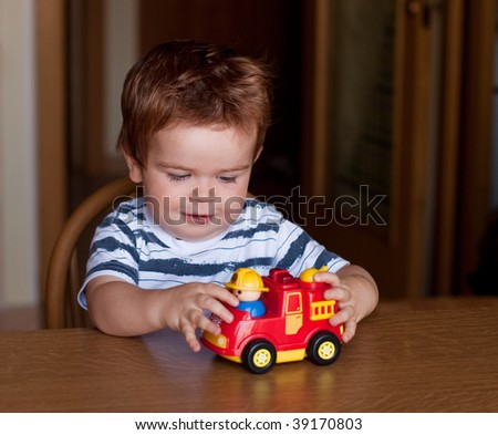 Child playing with a red car - stock photo