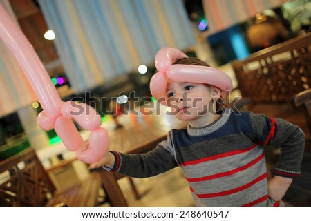 Child playing with balloon sword and helmet - stock photo