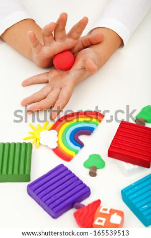 Child playing with colorful clay molding different shapes - closeup on hands - stock photo