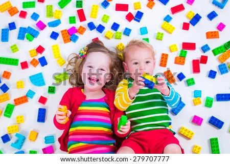Child playing with colorful toys. Little girl and baby boy with educational toy blocks. Children play at day care or preschool. Mess in kids room. View from above. - stock photo