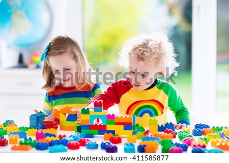 Child playing with colorful toys. Little girl and funny curly baby boy with educational toy blocks. Children play at day care or preschool. Mess in kids room. Toddlers build a tower in kindergarten. - stock photo