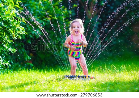 Child playing with garden sprinkler. Kid in bathing suit running and jumping. Kids gardening. Summer outdoor water fun. Children play with gardening hose watering flowers. - stock photo