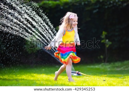 Child playing with garden sprinkler. Preschooler kid running and jumping. Summer outdoor water fun in the backyard. Children play with hose watering flowers. Kids run and splash on hot sunny day. - stock photo