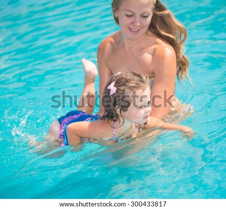 Child playing with mother in swimming pool - stock photo