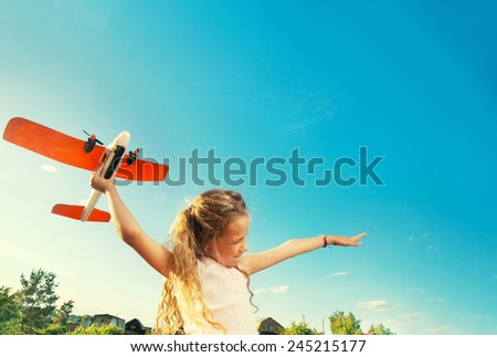 Child playing with plane. Happy girl play outdoors - stock photo