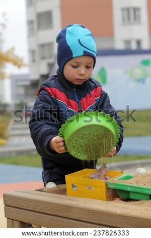 Child playing with sieve in sandbox in spring - stock photo