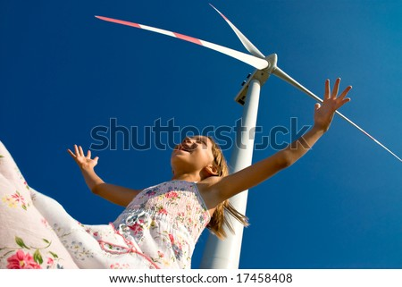 child playing with the wind near a wind turbine - stock photo