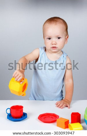 Child playing with toy plates and dishes in a blue dress smiling Studio - stock photo