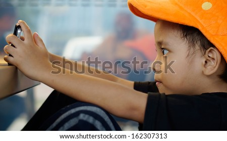 Child plays games on smartphone - stock photo