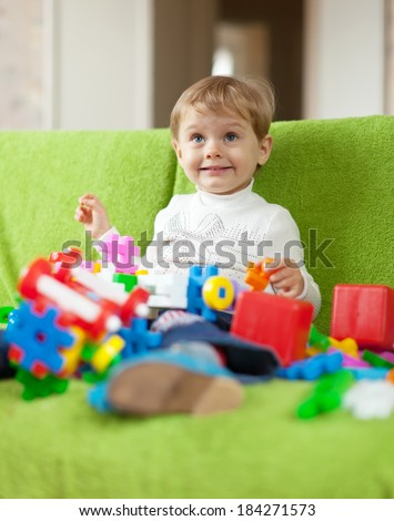 child plays with toys in home interior - stock photo