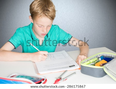 Child practicing English for an English work at school - stock photo