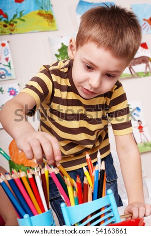 Child preschooler with pencil in play room. - stock photo