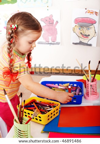 Child  prescooler with colour pencil in play room. - stock photo