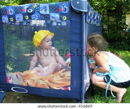 Child pressing face against play pen. - stock photo