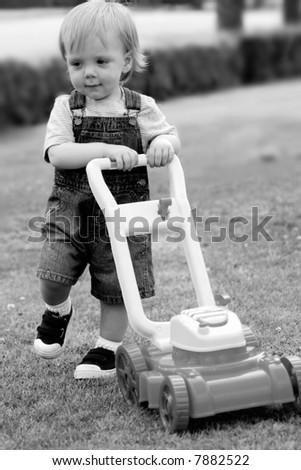 Child pretending to mow the lawn, black and white photo - stock photo