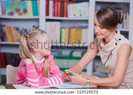 Child psychologist with a little girl, a child draws with colored pencils - stock photo