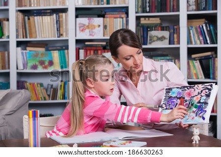 Child psychologist working with little girl's pictures - stock photo